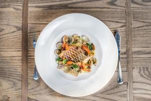 plato de mar de pescado loro al horno con zanahoria y ostras.