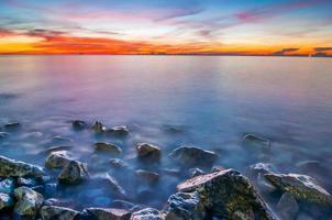 Light sunrise Sea waves lash impact rock on the beach.