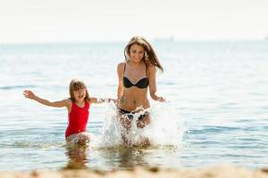 Little girl kid and woman mother in sea water. Fun