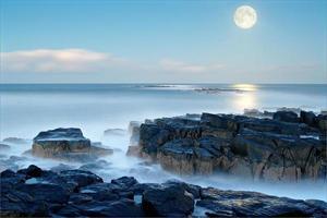 Moon rises smooth pale blue sea Snook Point Newton Northumberlan