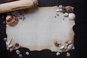 Old scroll of parchment with sea pebbles and seashells, nautical