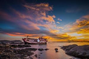 Fishing boat moored on the beach at sunset