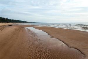 Shoreline of Baltic sea beach with rocks and sand dunes photo