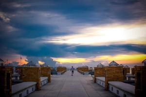 Magnificent long exposure sea sunset on pier and skateboarder rides