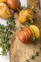 Sliced raw potatoes with sprigs of thyme, sea salt and