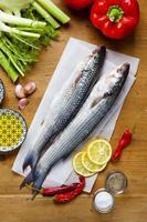 Pescado fresco crudo con ingredientes vegetales en una madera foto