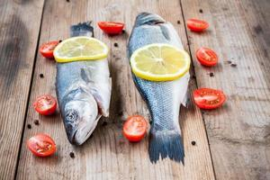 Two raw seabass fish with lemon and cherry tomatoes