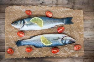 Two raw seabass fish with a lemon and cherry tomatoes