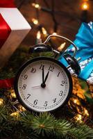 árbol de navidad, regalos, luces y reloj sobre la pared de madera