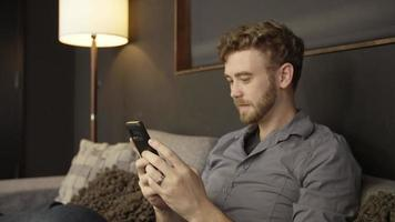 Slow motion of man texting on phone on sofa video