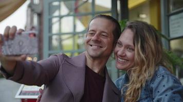 câmera lenta de casal tirando selfie na calçada da cafeteria