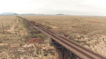 AERIAL: Two trains crossing steel arch railroad bridge across the Canyon Diablo