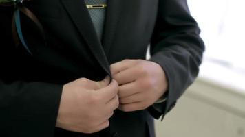 jovem noivo abotoa sua jaqueta na frente de um espelho