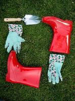garden gloves, spade and boots lying on green grass