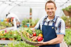 hombre sosteniendo una canasta de verduras frescas