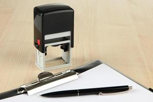 Stamp and clipboard on table