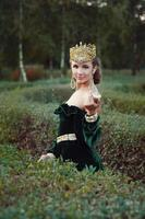 Elegant young woman dressed like queen walking in garden photo