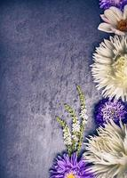 Composition of white dahlias and blue asters on dark background