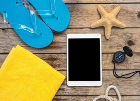 Wooden background with starfish, tablet and shell photo