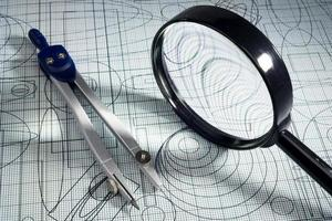 drawing,  magnifying glass and compasses, selective focus photo