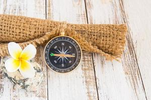 Close up compass and burlap sack on wooden background