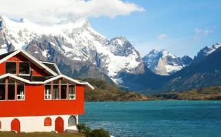 una casa roja en un lago en medio de las montañas foto
