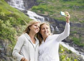 amigas tomando selfie en una cascada de montaña