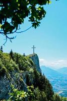 Green trees on mountain with cross