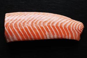 salmón pelado sobre fondo negro foto