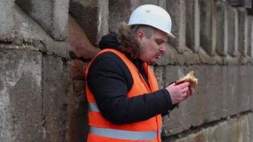 lavoratore che mangia hamburger all'aperto