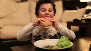 süßes Kind beißen köstlichen Hamburger