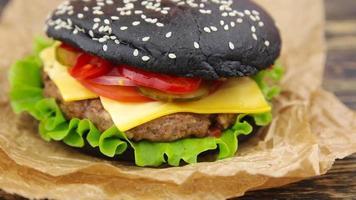 hambúrguer preto na mesa de madeira
