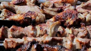 Chicken and pork grilled on charcoal in a barbecue. Meat rotates and has golden skin. moving the camera. Close up