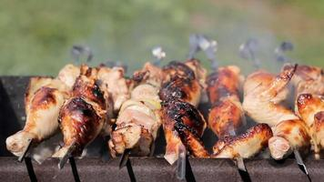 Chicken and pork grilled on charcoal in a barbecue. Meat rotates and has golden skin. moving the camera