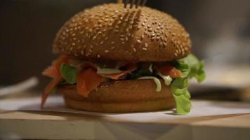 Mano con cuchillo y tenedor cortando pan y hamburguesa de ternera video