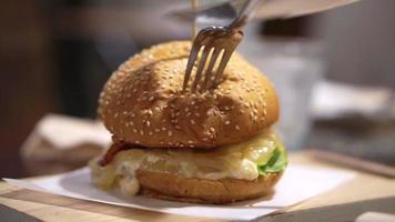 La main à l'aide d'un couteau et d'une fourchette de coupe de pain et hamburger
