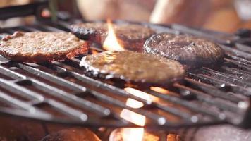 hambúrgueres em uma grelha com fogo sob video