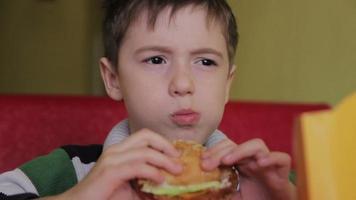 Boy eating a burger video