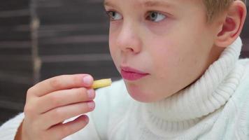 El niño come una papa frita en un restaurante de comida rápida closeup