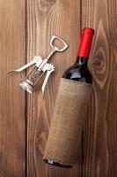 botella de vino tinto y sacacorchos foto