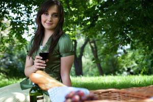 Portrait of young woman holding wineglass, sitting in park