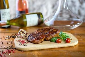 Filete de cerdo grande con especias, tomates y botellas de vino. foto
