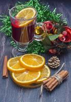 Hot wine (mulled wine) with spices on wooden background. photo