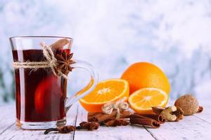 Mulled wine with oranges and spices on table