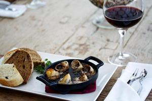 Plate of escargot snails on table with wine photo