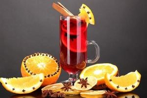 Fragrant mulled wine in glass with spices and oranges