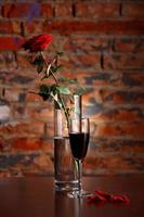Vase with rose and glass of wine