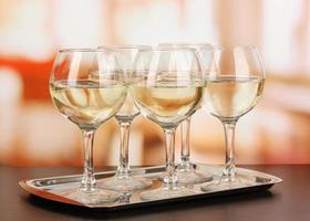 White wine in glass on room background photo