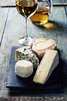 Various types of cheese and white wine photo