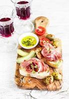 delicioso aperitivo al vino - tostadas con jamón, aceitunas, tomates